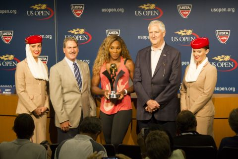 Legendary professional tennis player, Serena Williams, holding her prize from Emirates Airlines. Standing to Serena's right is David A. Haggerty, USTA, Chairman of the Board, CEO and President.