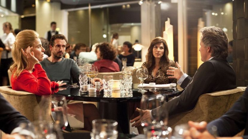 The Dinner cast members at dinner in a restaurant; Steve Coogan and Rebecca Hall, facing camera; Laura Linney (side-view) and Richard Gere with back to the camera.