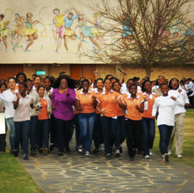 Oprah Winfrey walking briskly with students from the Oprah Winfrey Leadership Academy for Girls in South Africa. They are using Omron pedometers to keep track of their steps, as part of a fittest school challenge