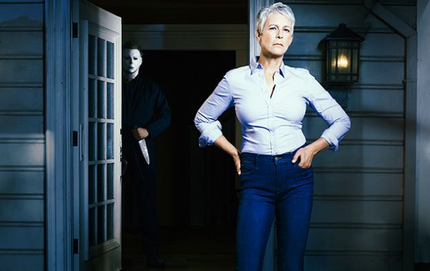 Laurie Strode (Jamie Lee Curtis) standing on the front porch of a house, while Mike Myers (Nick Castle) is behind her in the doorway holding a knife