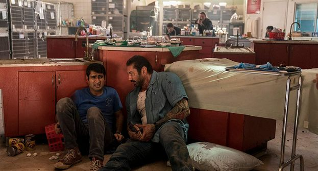 Kumail Nanjiani, as the Uber driver, and Dave Bautista, as the veteran cop, taking cover from the villain in the movie, Stuber.