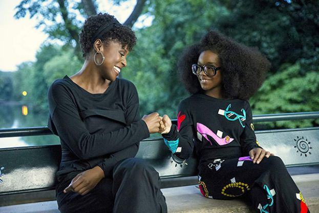 Issa Rae as April (left) and Marsai Martin, as her boss, Jordan Sanders, as a preteen girl, sitting on a park bench in the movie, Little.