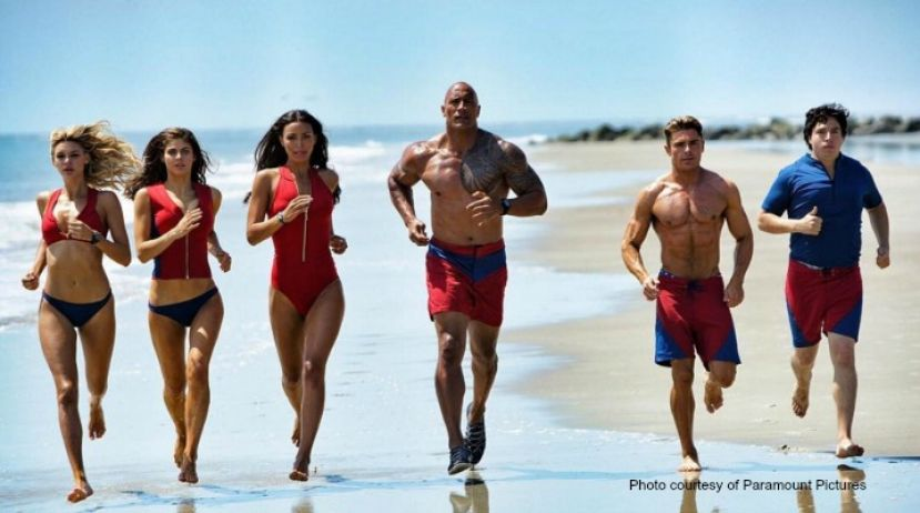 Baywatch cast from left to right: Kelly Rohrbach, Alexandra Daddario, Ifenesh Hadera, Dwayne Johnson, Zac Efron, and Jon Bass