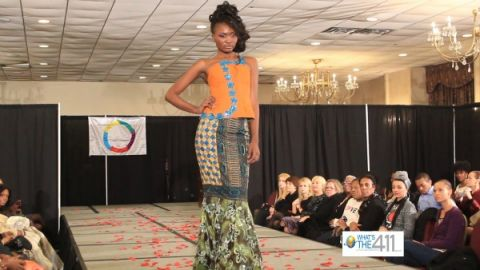 African Elegance Fashion Show model walking the runway in a African print top and long fishtail skirt