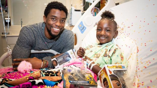 Actor,Chadwick Boseman, succumbs to colon cancer at age 42. In this photo, Boseman brings a smile to a child at St. Jude's hospital.